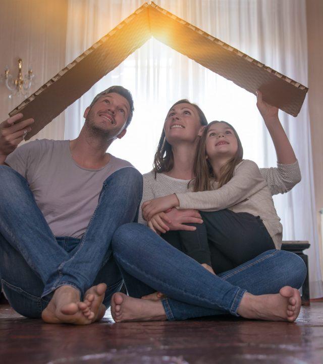 Familie mit Haus im Wohnzimmer mit Hildebrand-Immobilien